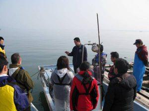 鏡町漁業協同組合のカキ養殖施設で関係者と意見を交わす参加者